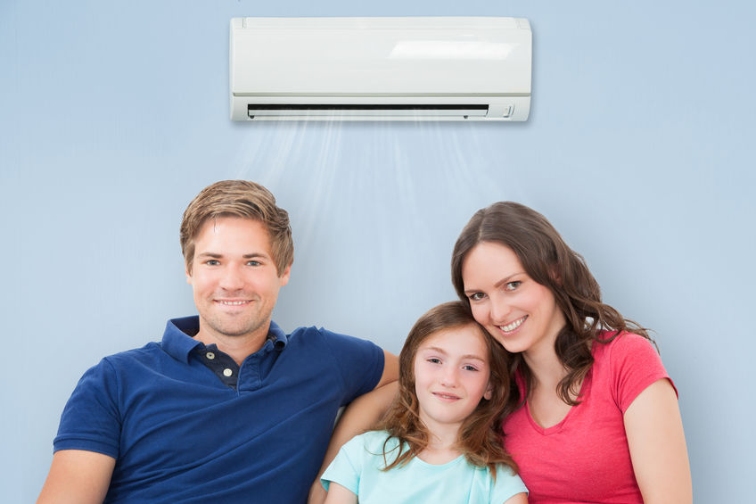 Family Sitting On Sofa Under Air Conditioning