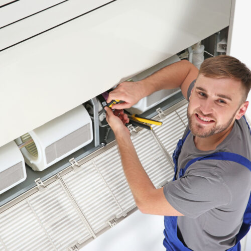 HVAC technician repairing air conditioner in Knoxville, TN.